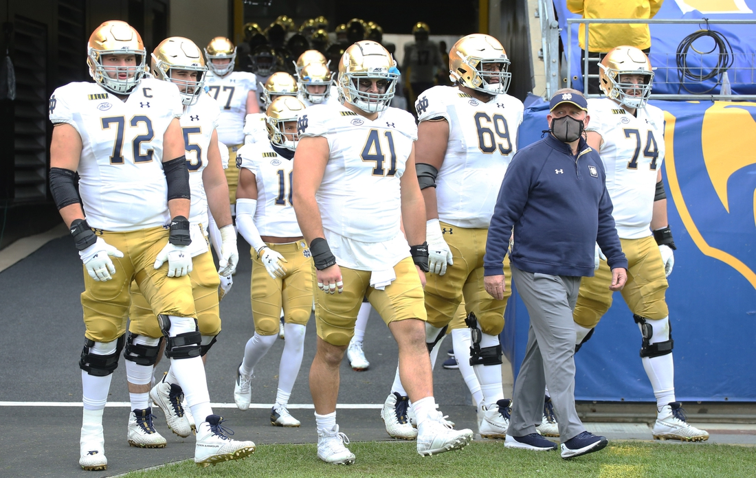 Oct 24, 2020; Pittsburgh, Pennsylvania, USA;  Notre Dame Fighting Irish head coach Brian Kelly (right) leads the team onto the field before playing the Pittsburgh Panthers at Heinz Field. Notre Dame won 45-3. Mandatory Credit: Charles LeClaire-USA TODAY Sports