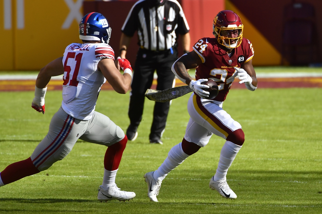 Nov 8, 2020; Landover, Maryland, USA;  Washington Football Team running back Antonio Gibson (24) carries the ball as New York Giants linebacker Kyler Fackrell (51) defends during the first quarter at FedExField. Mandatory Credit: Brad Mills-USA TODAY Sports