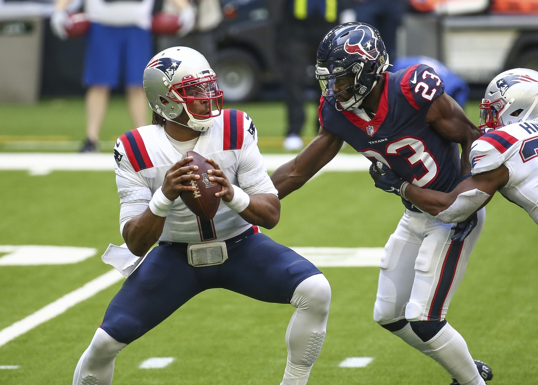 Nov 22, 2020; Houston, Texas, USA; New England Patriots quarterback Cam Newton (1) looks for an open receiver as Houston Texans free safety Eric Murray (23) applies defensive pressure during the second quarter at NRG Stadium. Mandatory Credit: Troy Taormina-USA TODAY Sports