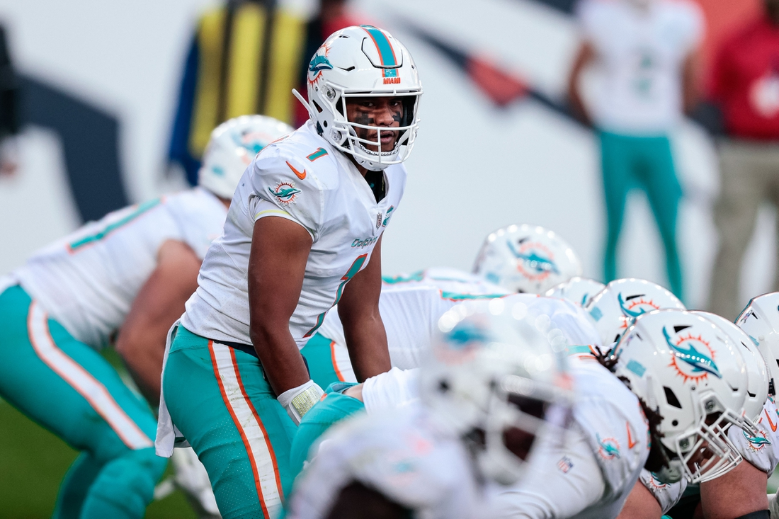 Nov 22, 2020; Denver, Colorado, USA; Miami Dolphins quarterback Tua Tagovailoa (1) at the line of scrimmage in the third quarter against the Denver Broncos at Empower Field at Mile High. Mandatory Credit: Isaiah J. Downing-USA TODAY Sports