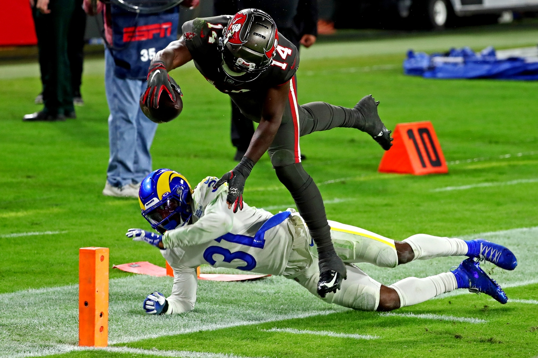 Nov 23, 2020; Tampa, Florida, USA;  Tampa Bay Buccaneers wide receiver Chris Godwin (14) dives for a touchdown  against Los Angeles Rams defensive back Darious Williams (31) during the fourth quarter at Raymond James Stadium. Mandatory Credit: Kim Klement-USA TODAY Sports