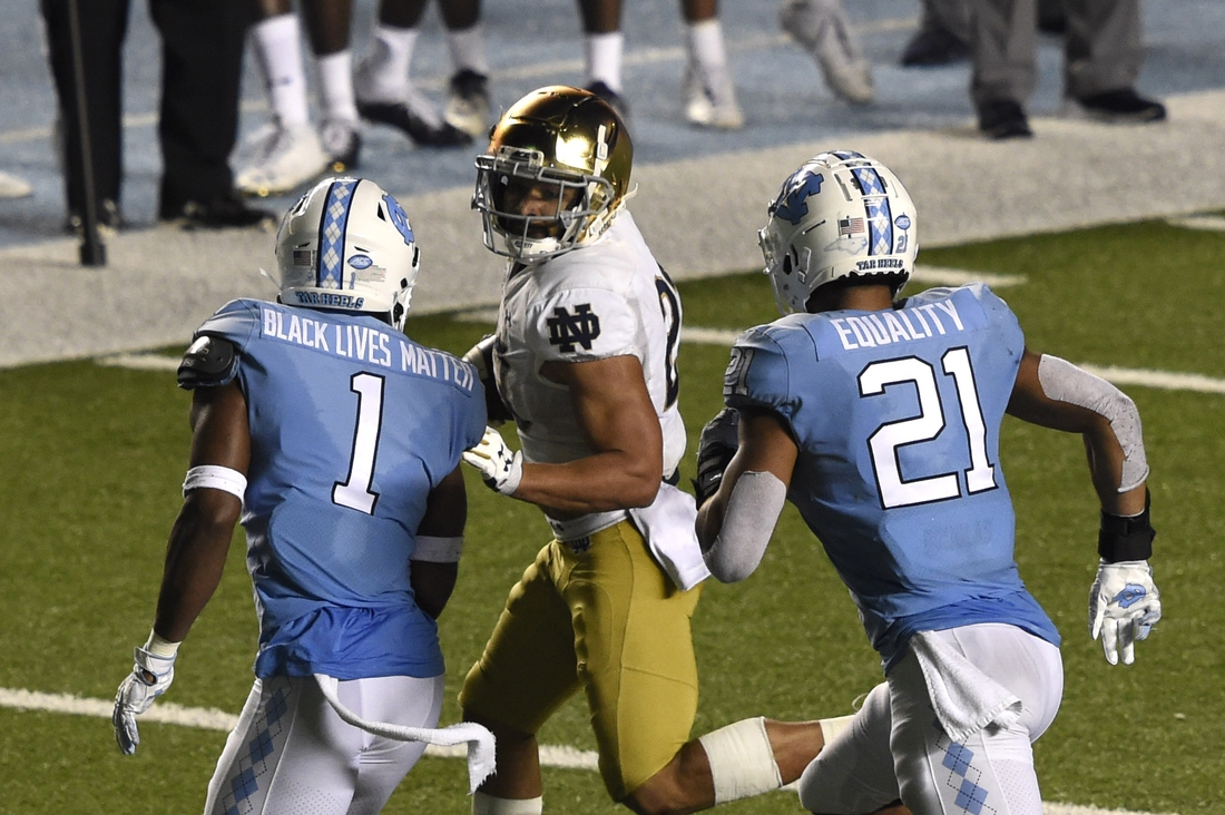 Nov 27, 2020; Chapel Hill, North Carolina, USA; Notre Dame Fighting Irish running back Kyren Williams (23) with the ball as North Carolina Tar Heels defensive back Kyler McMichael (1) and linebacker Chazz Surratt (21) defend in the fourth quarter at Kenan Memorial Stadium. Mandatory Credit: Bob Donnan-USA TODAY Sports