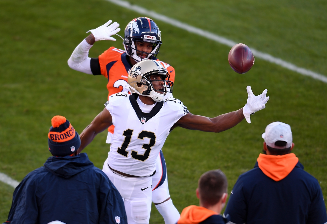 Nov 29, 2020; Denver, Colorado, USA; New Orleans Saints wide receiver Michael Thomas (13) is unable to control the ball as Denver Broncos cornerback A.J. Bouye (21) defends in the first quarter at Empower Field at Mile High. Mandatory Credit: Ron Chenoy-USA TODAY Sports