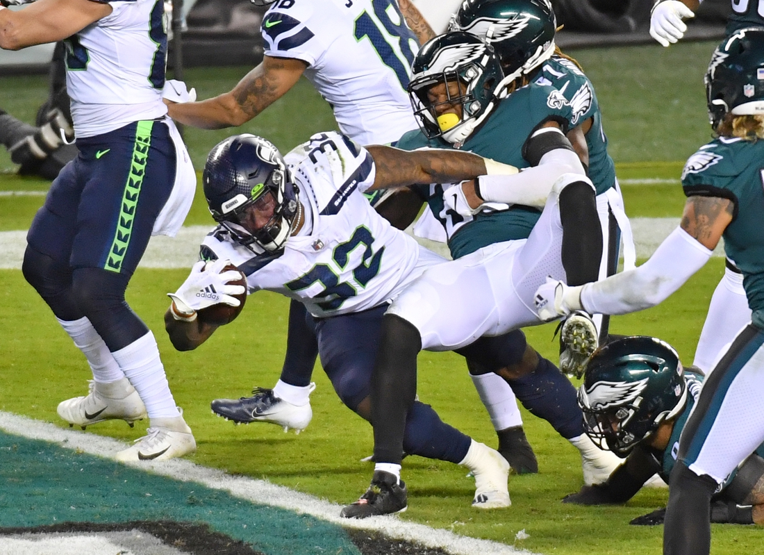 Nov 30, 2020; Philadelphia, Pennsylvania, USA; Seattle Seahawks running back Chris Carson (32) reaches across the the goal line for a touchdown against Philadelphia Eagles free safety Rodney McLeod (23) during the second quarter at Lincoln Financial Field. Mandatory Credit: Eric Hartline-USA TODAY Sports