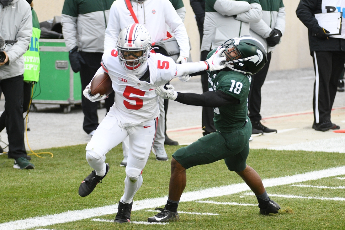 Dec 5, 2020; East Lansing, Michigan, USA; Ohio State Buckeyes wide receiver Garrett Wilson (5) stiff arms Michigan State Spartans cornerback Kalon Gervin (18) to run for a touchdown during the first quarter at Spartan Stadium. Mandatory Credit: Tim Fuller-USA TODAY Sports