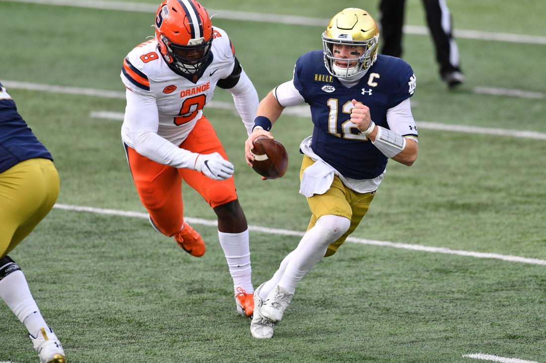 Dec 5, 2020; South Bend, Indiana, USA; Notre Dame Fighting Irish quarterback Ian Book (12) runs as Syracuse Orange wide receiver Sharod Johnson (8) pursues in the second quarter at Notre Dame Stadium. Mandatory Credit: Matt Cashore-USA TODAY Sports