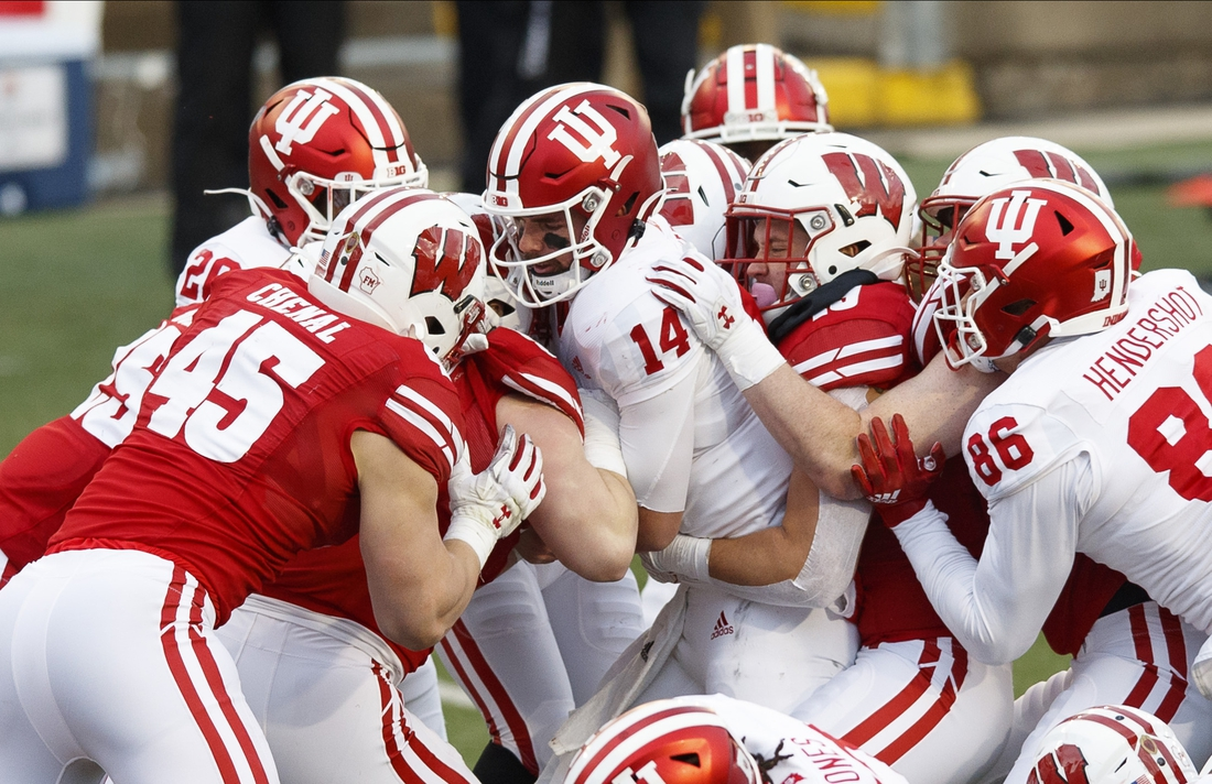 Dec 5, 2020; Madison, Wisconsin, USA;  Indiana Hoosiers quarterback Jack Tuttle (14) is tackled with the football during the second quarter against the Wisconsin Badgers at Camp Randall Stadium. Mandatory Credit: Jeff Hanisch-USA TODAY Sports