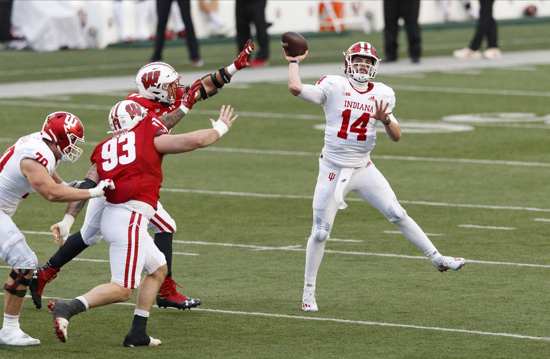 Dec 5, 2020; Madison, Wisconsin, USA;  Indiana Hoosiers quarterback Jack Tuttle (14) throws a pass under pressure from Wisconsin Badgers defensive end Garrett Rand (93) and Wisconsin Badgers defensive end Isaiahh Loudermilk (97) during the second quarter at Camp Randall Stadium. Mandatory Credit: Jeff Hanisch-USA TODAY Sports
