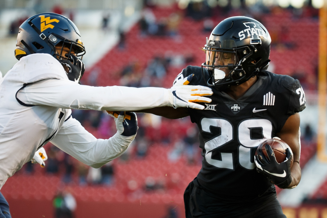 Dec 5, 2020; Ames, Iowa, USA; Iowa State running back Breece Hall (28) gets away from West Virginia linebacker Tony Fields II (1) during their football game at Jack Trice Stadium on Saturday. Iowa State takes a 21-0 lead over West Virginia into halftime. Mandatory Credit: Brian Powers-USA TODAY Sports