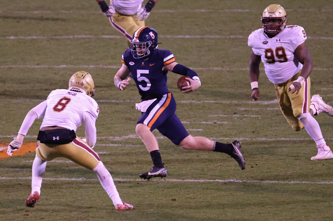 Dec 5, 2020; Charlottesville, Virginia, USA; Virginia Cavaliers quarterback Brennan Armstrong (5) runs with the ball past Boston College Eagles defensive back Jahmin Muse (8) en route to a touchdown in the third quarter at Scott Stadium. Mandatory Credit: Geoff Burke-USA TODAY Sports
