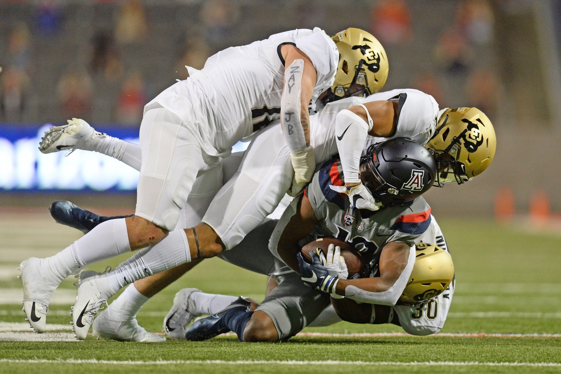Dec 5, 2020; Tucson, Arizona, USA; Arizona Wildcats wide receiver Jamarye Joiner (10) is tackled by Colorado Buffaloes defenders during the first half at Arizona Stadium. Mandatory Credit: Joe Camporeale-USA TODAY Sports