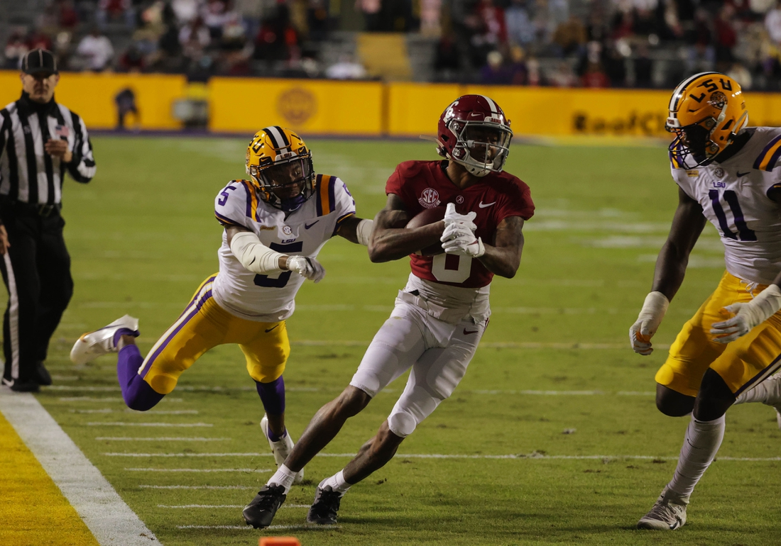 Dec 5, 2020; Baton Rouge, Louisiana, USA; Alabama Crimson Tide wide receiver DeVonta Smith (6) is pursued by LSU Tigers cornerback Jay Ward (5) and defensive lineman Ali Gaye (11) during the first quarter at Tiger Stadium. Mandatory Credit: Derick E. Hingle-USA TODAY Sports