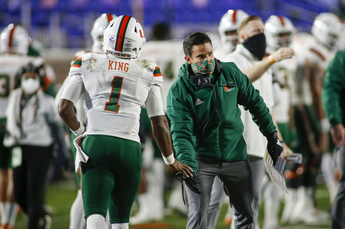 Dec 5, 2020; Durham, North Carolina, USA;  Miami Hurricanes head coach Manny Diaz (right) congratulates quarterback D'Eriq King (1) after a touchdown pass against the Duke Blue Devils in the first quarter at Wallace Wade Stadium. Mandatory Credit: Nell Redmond-USA TODAY Sports