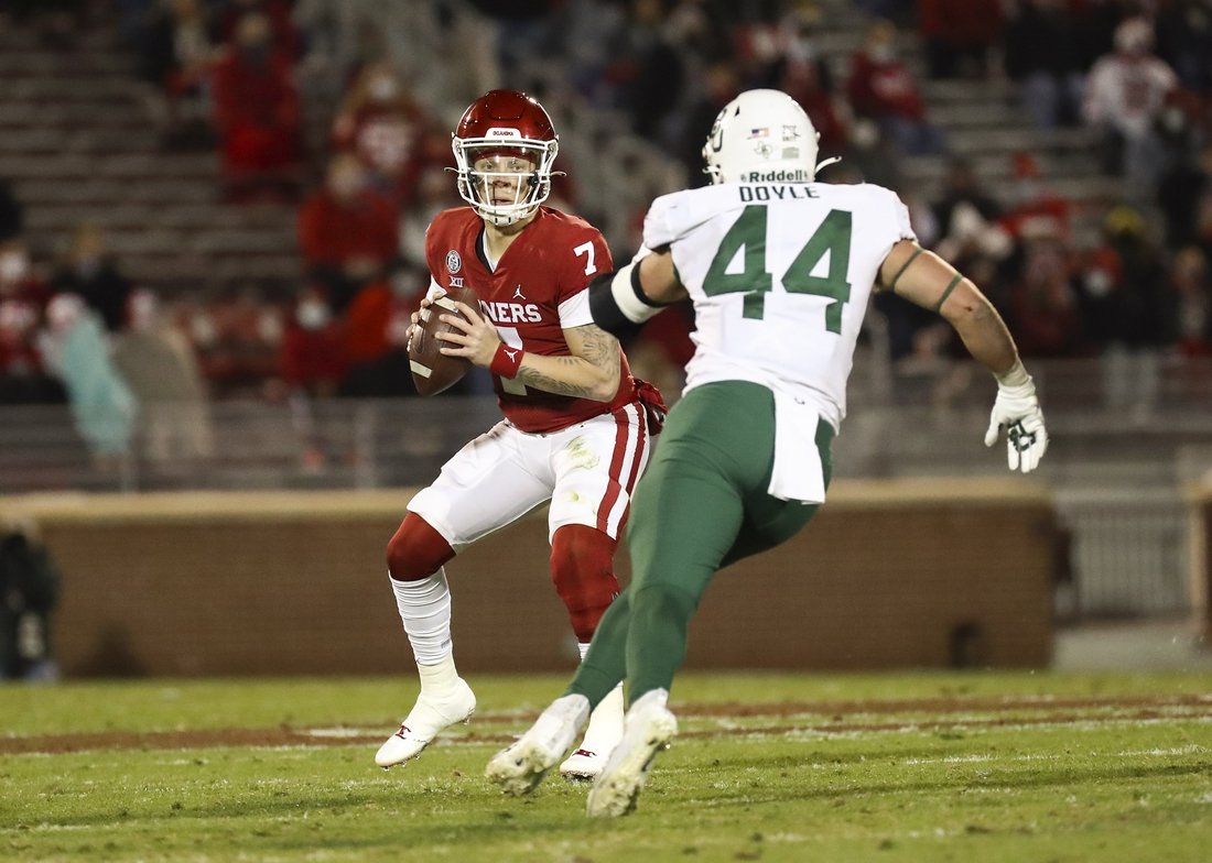 Dec 5, 2020; Norman, Oklahoma, USA; Oklahoma Sooners quarterback Spencer Rattler (7) throws as Baylor Bears linebacker Dillon Doyle (44) chases during the first half at Gaylord Family-Oklahoma Memorial Stadium. Mandatory Credit: Kevin Jairaj-USA TODAY Sports