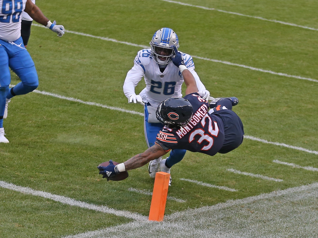 Dec 6, 2020; Chicago, Illinois, USA; Chicago Bears running back David Montgomery (32) scores a touchdown with Detroit Lions strong safety Duron Harmon (26) defending during the first quarter at Soldier Field. Mandatory Credit: Dennis Wierzbicki-USA TODAY Sports