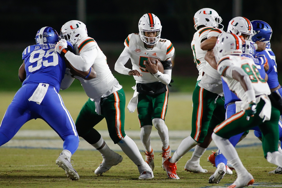 Dec 5, 2020; Durham, North Carolina, USA;  Miami Hurricanes quarterback N'Kosi Perry (5) carries the football against the Duke Blue Devils in the second half at Wallace Wade Stadium. The Miami Hurricanes won 48-0. Mandatory Credit: Nell Redmond-USA TODAY Sports