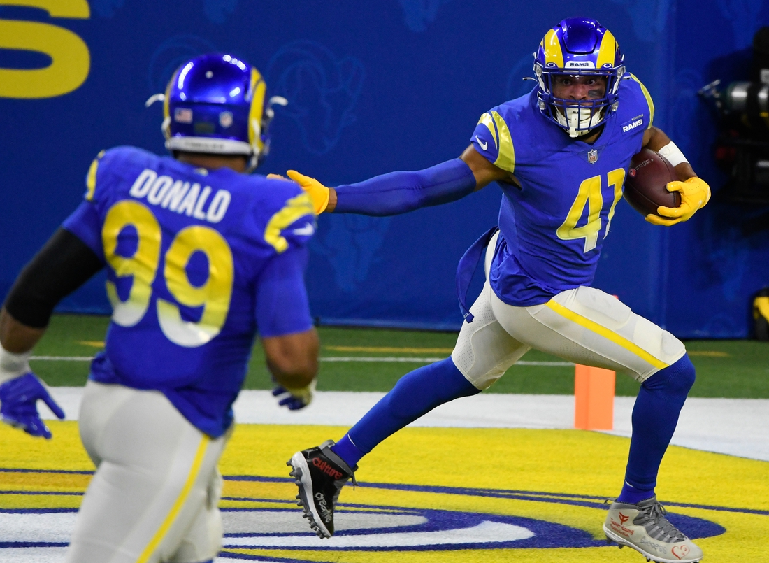 Dec 10, 2020; Inglewood, California, USA; Los Angeles Rams outside linebacker Kenny Young (41) runs back an interception for a touchdown against the New England Patriots in the second quarter at SoFi Stadium. Mandatory Credit: Robert Hanashiro-USA TODAY Sports
