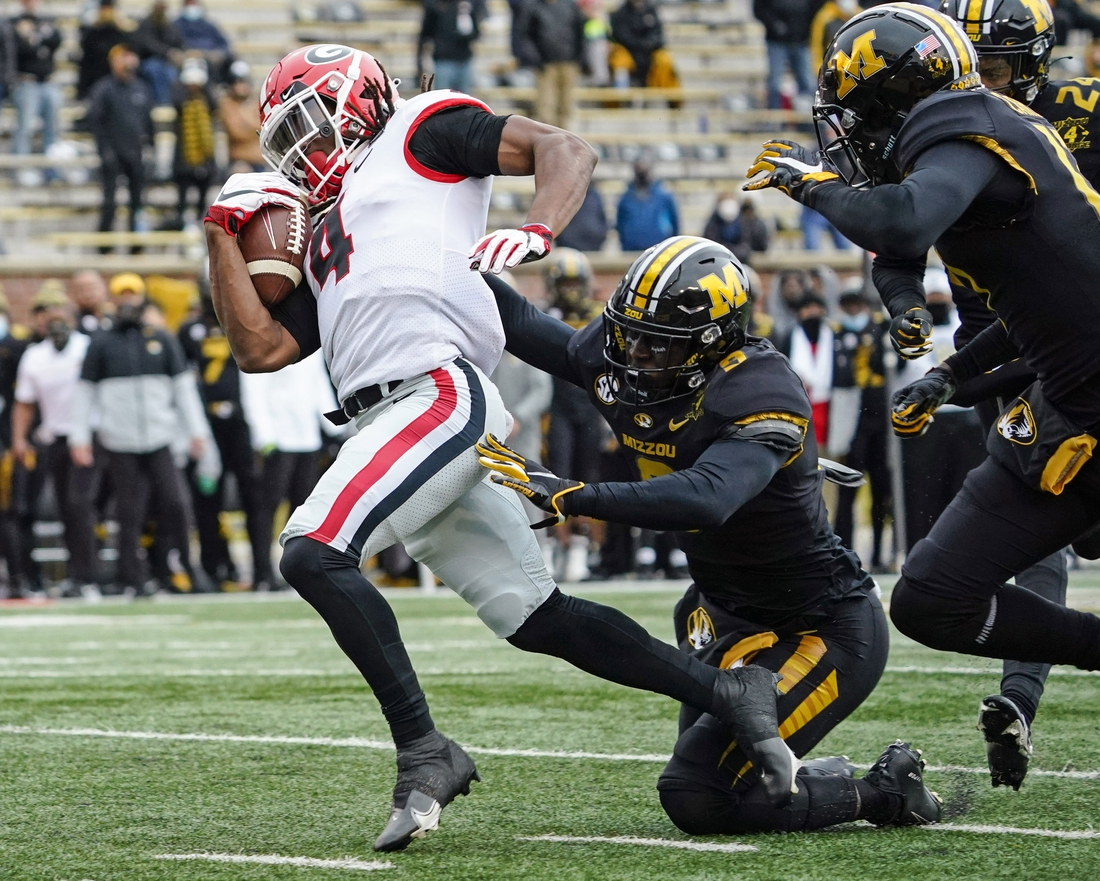 Dec 12, 2020; Columbia, Missouri, USA; Georgia Bulldogs running back James Cook (4) runs for a touchdown against Missouri Tigers safety Tyree Gillespie (9) during the first half at Faurot Field at Memorial Stadium. Mandatory Credit: Jay Biggerstaff-USA TODAY Sports
