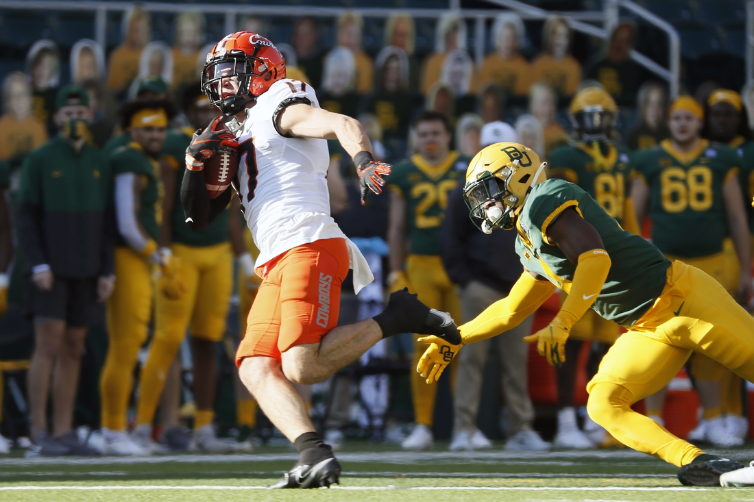 Dec 12, 2020; Waco, Texas, USA; Oklahoma State Cowboys wide receiver Dillon Stoner (17) runs past Baylor Bears safety Christian Morgan (4) on a 75-yard touchdown reception during the first half at McLane Stadium. Mandatory Credit: Raymond Carlin III-USA TODAY Sports