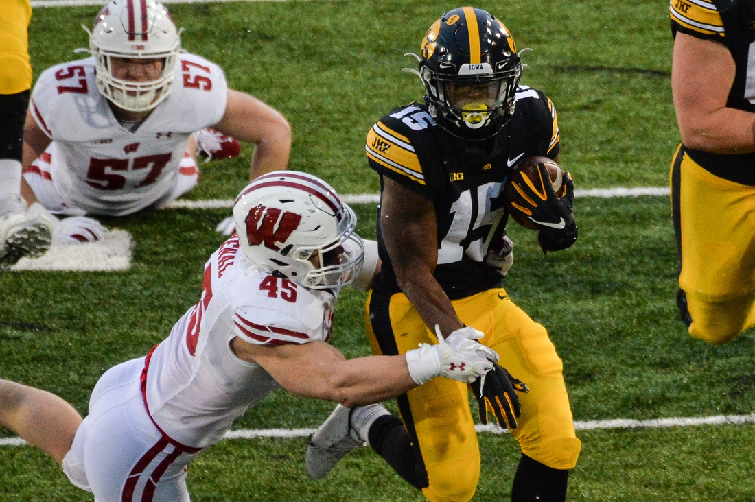 Dec 12, 2020; Iowa City, Iowa, USA; Iowa Hawkeyes running back Tyler Goodson (15) runs the ball as Wisconsin Badgers linebacker Leo Chenal (45) makes the tackle during the second quarter at Kinnick Stadium. Mandatory Credit: Jeffrey Becker-USA TODAY Sports