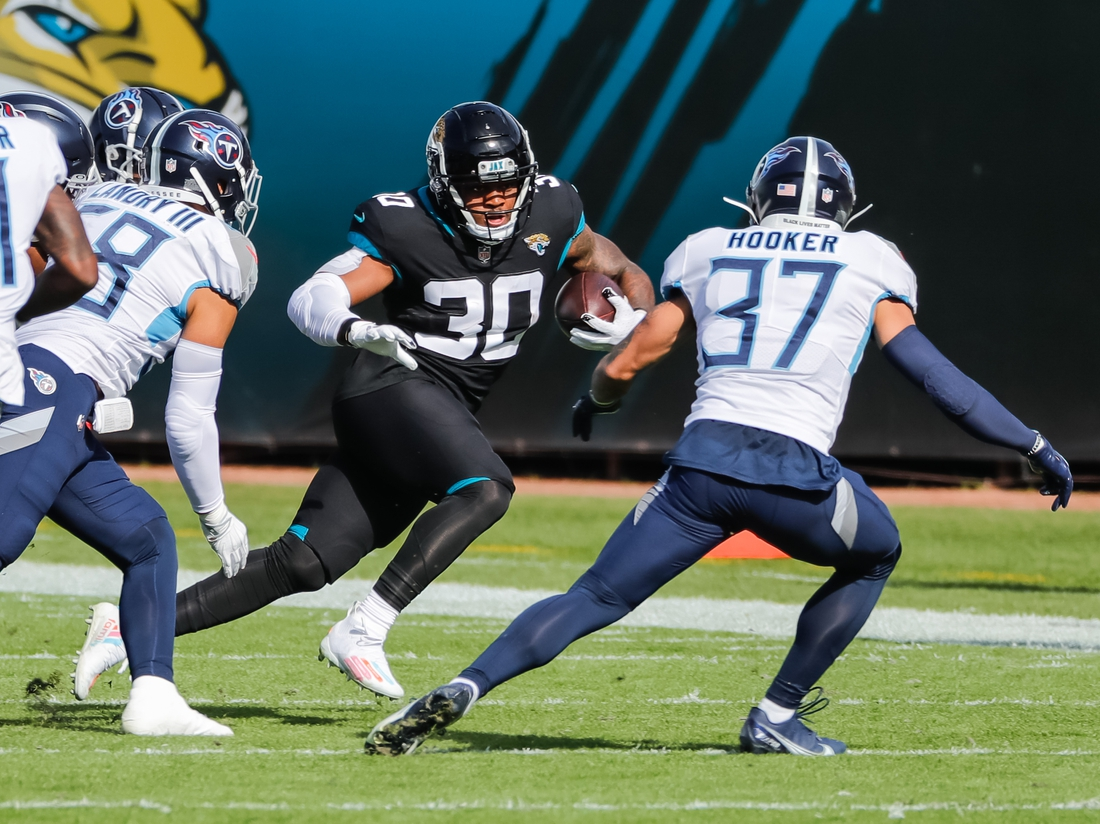 Dec 13, 2020; Jacksonville, Florida, USA; Jacksonville Jaguars running back James Robinson (30) carries the ball against Tennessee Titans strong safety Amani Hooker (37) during the first quarter at TIAA Bank Field. Mandatory Credit: Mike Watters-USA TODAY Sports