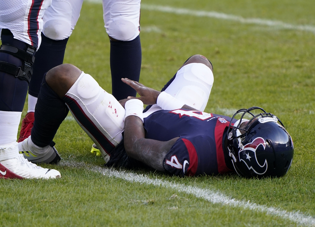 Dec 13, 2020; Chicago, Illinois, USA; Houston Texans quarterback Deshaun Watson (4) lays on the ground after being hit by Chicago Bears inside linebacker Roquan Smith (not pictured) during the third quarter at Soldier Field. Mandatory Credit: Mike Dinovo-USA TODAY Sports