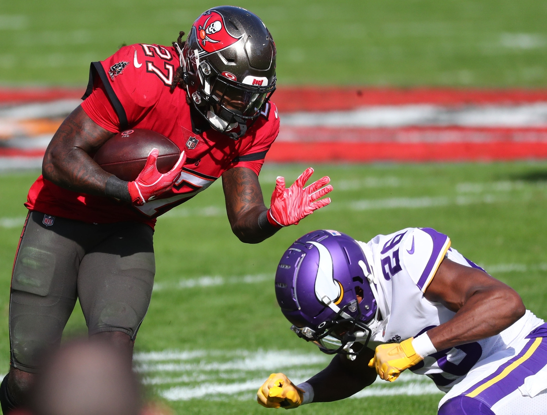 Dec 13, 2020; Tampa, Florida, USA; Tampa Bay Buccaneers running back Ronald Jones (27) runs with the ball as Minnesota Vikings defensive back Chris Jones (26) defends during the second quarter at Raymond James Stadium. Mandatory Credit: Kim Klement-USA TODAY Sports