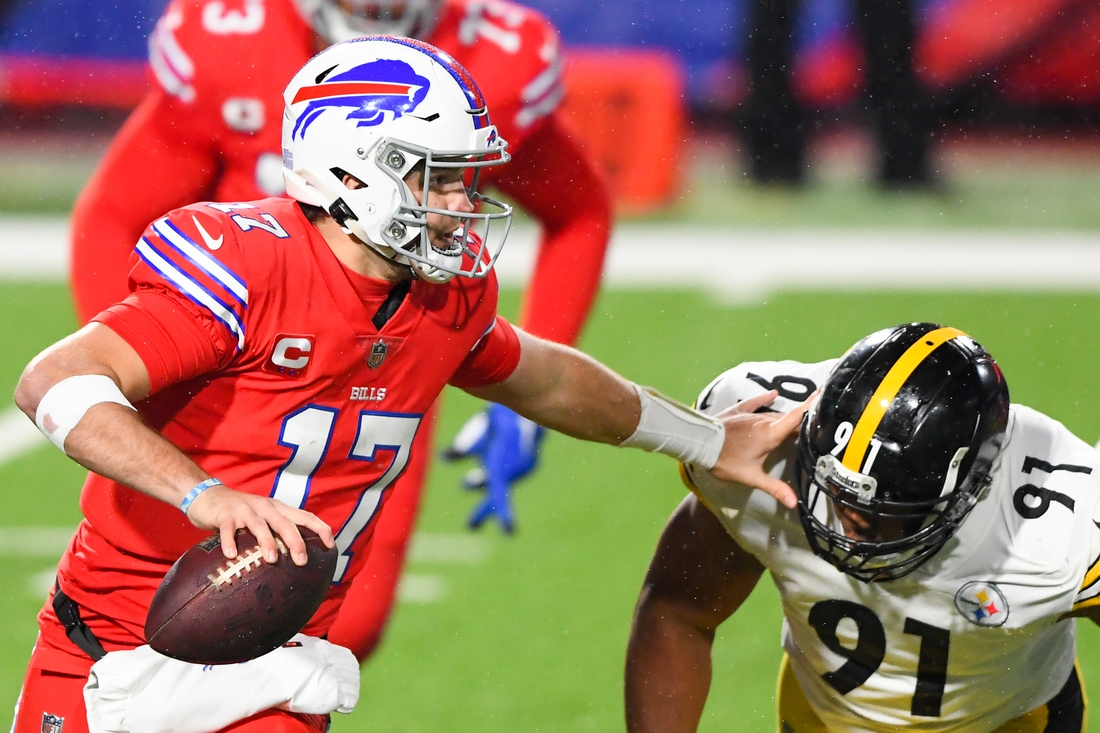 Dec 13, 2020; Orchard Park, New York, USA; Buffalo Bills quarterback Josh Allen (17) avoids Pittsburgh Steelers defensive end Stephon Tuitt (91) while running with the ball during the second quarter at Bills Stadium. Mandatory Credit: Rich Barnes-USA TODAY Sports