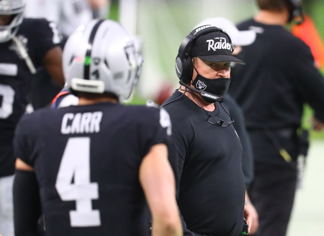 Dec 13, 2020; Paradise, Nevada, USA; Las Vegas Raiders head coach Jon Gruden looks at quarterback Derek Carr against the Indianapolis Colts during the second half at Allegiant Stadium. Mandatory Credit: Mark J. Rebilas-USA TODAY Sports