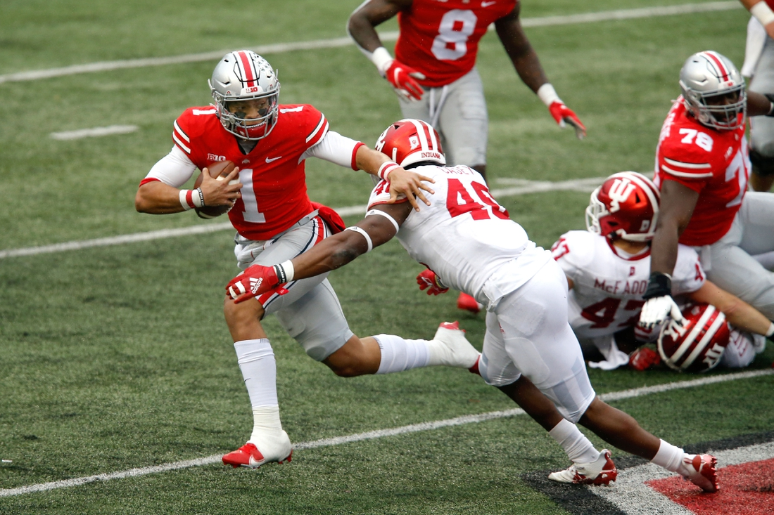 Nov 21, 2020; Columbus, Ohio, USA; Ohio State Buckeyes quarterback Justin Fields (1) runs as he breaks the tackle of Indiana Hoosiers linebacker Aaron Casey (46) during the second quarter at Ohio Stadium. Mandatory Credit: Joseph Maiorana-USA TODAY Sports