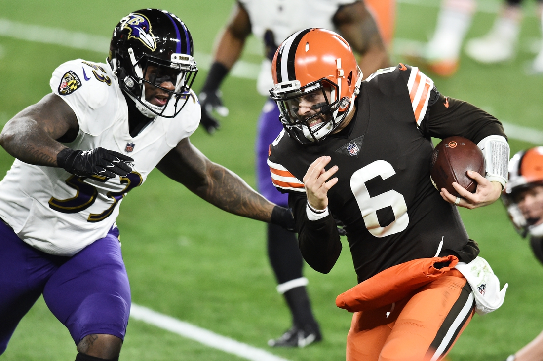 Dec 14, 2020; Cleveland, Ohio, USA; Cleveland Browns quarterback Baker Mayfield (6) runs with the ball as Baltimore Ravens defensive end Jihad Ward (53) defends during the first quarter at FirstEnergy Stadium. Mandatory Credit: Ken Blaze-USA TODAY Sports