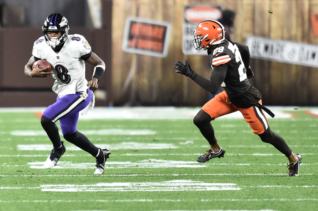 Dec 14, 2020; Cleveland, Ohio, USA; Cleveland Browns cornerback Kevin Johnson (28) chases Baltimore Ravens quarterback Lamar Jackson (8) during the first quarter at FirstEnergy Stadium. Mandatory Credit: Ken Blaze-USA TODAY Sports