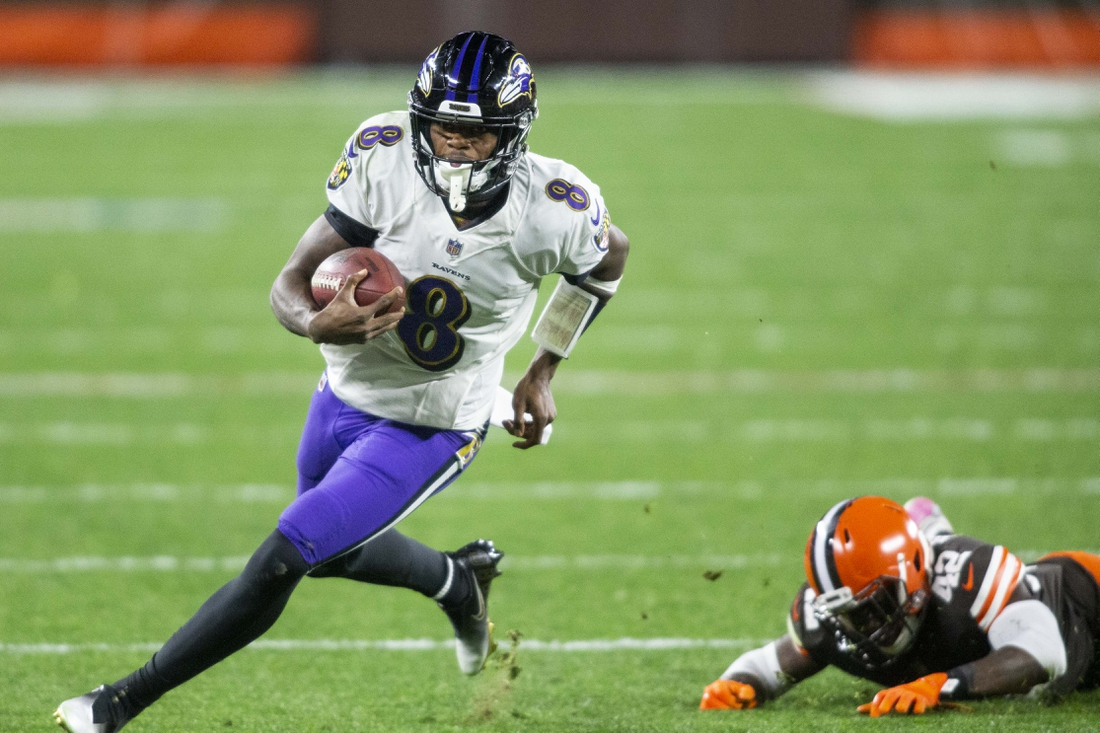 Dec 14, 2020; Cleveland, Ohio, USA; Baltimore Ravens quarterback Lamar Jackson (8) runs the ball past Cleveland Browns strong safety Karl Joseph (42) during the second quarter at FirstEnergy Stadium. Mandatory Credit: Scott Galvin-USA TODAY Sports