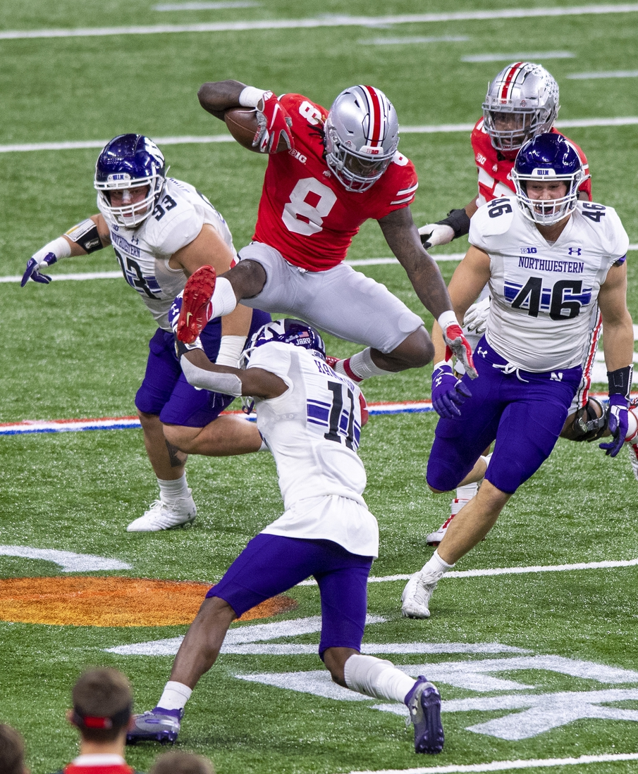Dec 19, 2020; Indianapolis, Indiana, USA;  Ohio State Buckeyes running back Trey Sermon (8) leaps over Northwestern Wildcats defensive back A.J. Hampton (11) during the first half of the Big Ten Championship game at Lucas Oil Stadium. Mandatory Credit: Doug McSchooler-USA TODAY Sports