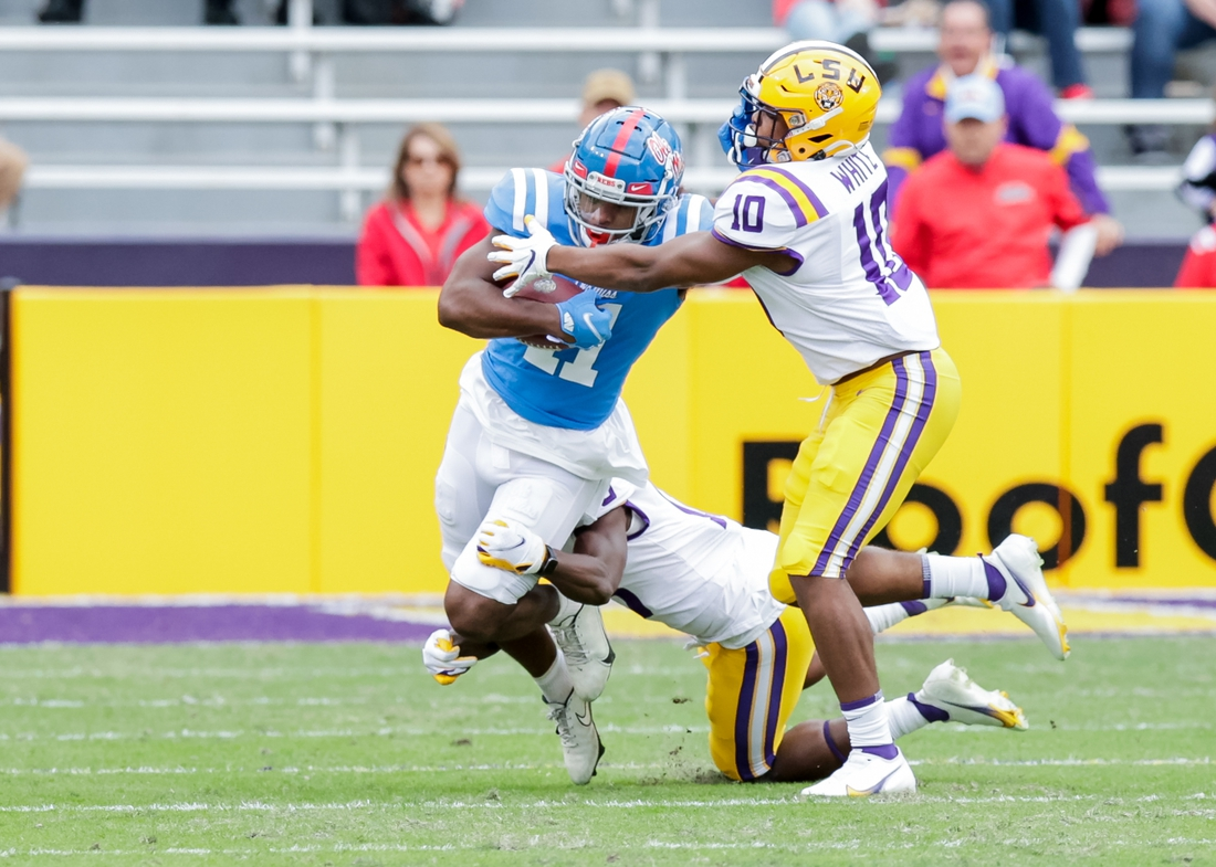 Dec 19, 2020; Baton Rouge, Louisiana, USA;  Mississippi Rebels wide receiver Dontario Drummond (11) is tackled by LSU Tigers linebacker Josh White (10) at Tiger Stadium. Mandatory Credit: Stephen Lew-USA TODAY Sports