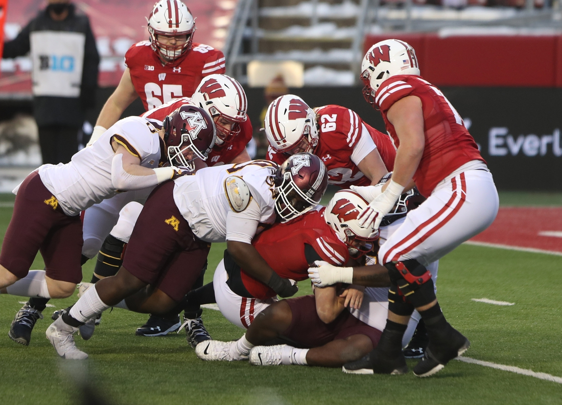 Dec 19, 2020; Madison, Wisconsin, USA; DUPLICATE***Wisconsin Badgers quarterback Graham Mertz (5)is sacked by the  Minnesota Golden Gophers defense during the first  half at Camp Randall Stadium. Mandatory Credit: Mary Langenfeld-USA TODAY Sports