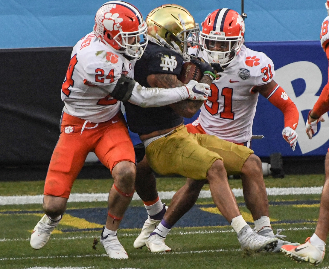 Dec 19, 2020; Charlotte, NC, USA; Clemson safety Nolan Turner (24) and cornerback Mario Goodrich (31) tackle Notre Dame running back Kyren Williams (23) during the first quarter of the ACC Championship game  at Bank of America Stadium. Mandatory Credit: Ken Ruinard-USA TODAY Sports