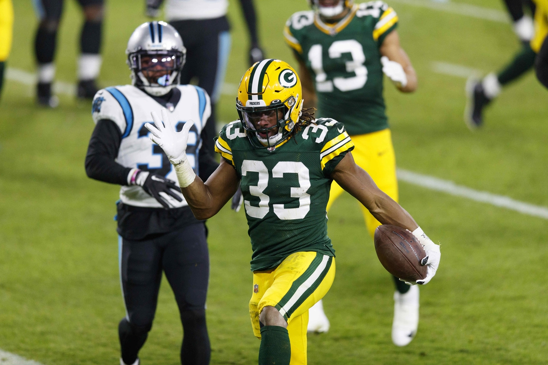 Dec 19, 2020; Green Bay, Wisconsin, USA;  Green Bay Packers running back Aaron Jones (33) celebrates after scoring a touchdown during the second quarter against the Carolina Panthers at Lambeau Field. Mandatory Credit: Jeff Hanisch-USA TODAY Sports