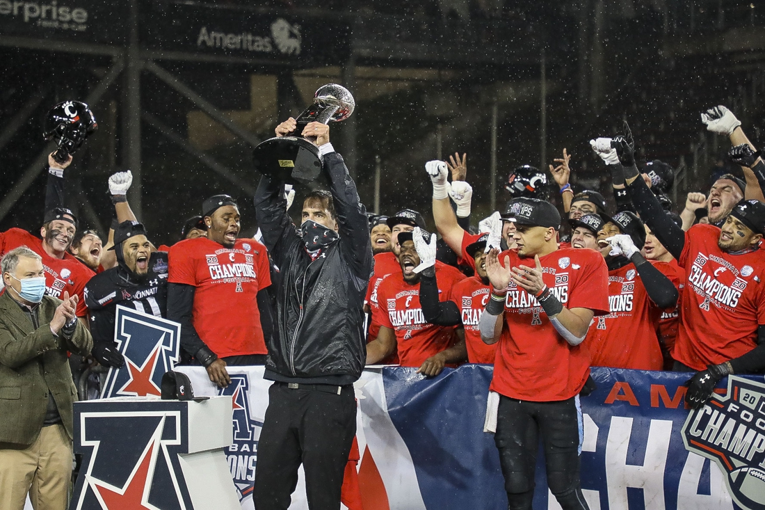 Dec 19, 2020; Cincinnati, Ohio, USA; Cincinnati Bearcats head coach Luke Fickell holds up the AAC Championship trophy at the end of the game against the Tulsa Golden Hurricane at Nippert Stadium. Mandatory Credit: Katie Stratman-USA TODAY Sports