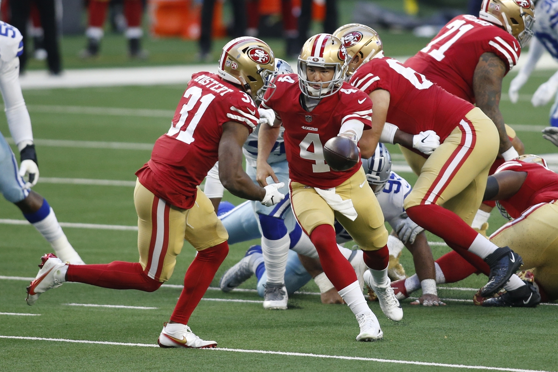 Dec 20, 2020; Arlington, Texas, USA; San Francisco 49ers quarterback Nick Mullens (4) hands off to running back Raheem Mostert (31) against the Dallas Cowboys in the first quarter at AT&T Stadium. Mandatory Credit: Tim Heitman-USA TODAY Sports