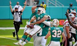 Dec 20, 2020; Miami Gardens, Florida, USA; Miami Dolphins quarterback Tua Tagovailoa (1) celebrates with teammates after scoring a touchdown against the New England Patriots during the second half at Hard Rock Stadium. Mandatory Credit: Jasen Vinlove-USA TODAY Sports