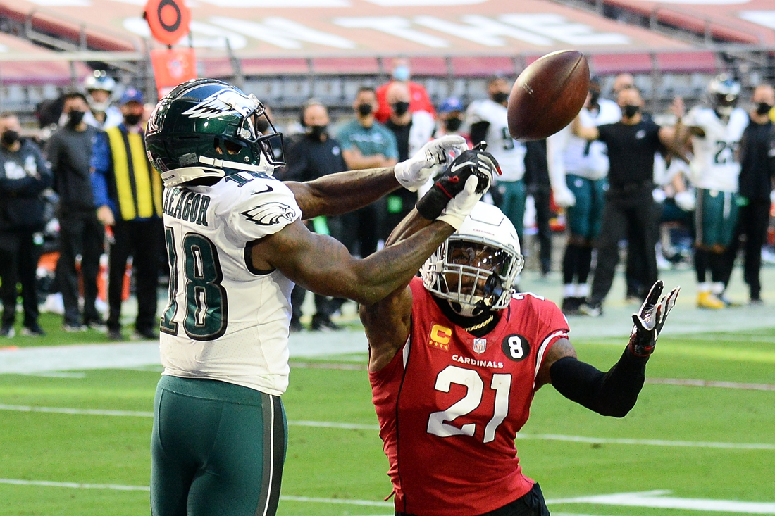 Dec 20, 2020; Glendale, Arizona, USA; Arizona Cardinals cornerback Patrick Peterson (21) break up a pass intended for Philadelphia Eagles wide receiver Jalen Reagor (18) during the first half at State Farm Stadium. Mandatory Credit: Joe Camporeale-USA TODAY Sports