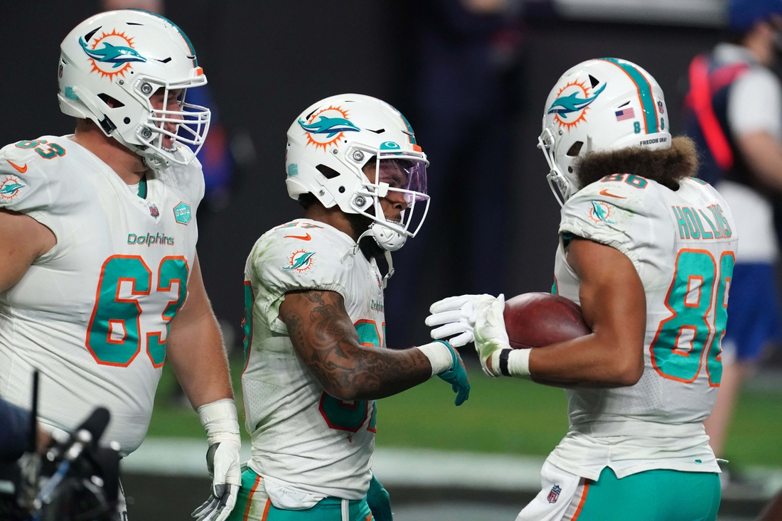 Dec 26, 2020; Paradise, Nevada, USA; Miami Dolphins running back Myles Gaskin (37) celebrates with center Michael Deiter (63( and tight end Mike Gesicki (88) after scoring a 59-yard touchdown reception in the fourth quarter at Allegiant Stadium. The Dolphins defeated the Raiders 26-25. Mandatory Credit: Kirby Lee-USA TODAY Sports