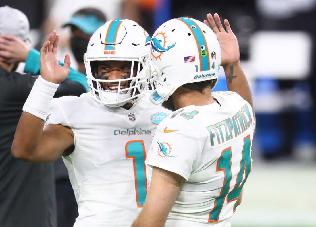 Dec 26, 2020; Paradise, Nevada, USA; Miami Dolphins quarterback Tua Tagovailoa (1) with Ryan Fitzpatrick (14) against the Las Vegas Raiders at Allegiant Stadium. Mandatory Credit: Mark J. Rebilas-USA TODAY Sports
