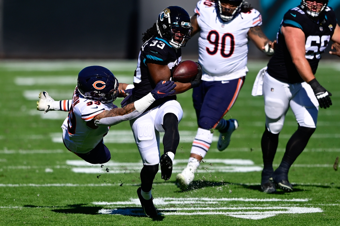 Dec 27, 2020; Jacksonville, Florida, USA; Jacksonville Jaguars running back Dare Ogunbowale (33) runs the ball against Chicago Bears linebacker Trevis Gipson (99) during the first half at TIAA Bank Field. Mandatory Credit: Douglas DeFelice-USA TODAY Sports