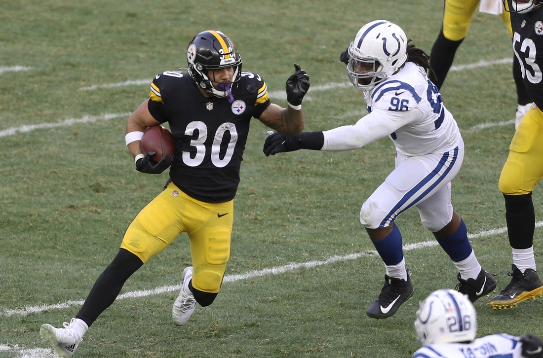 Dec 27, 2020; Pittsburgh, Pennsylvania, USA;  Pittsburgh Steelers running back James Conner (30) carries the ball against Indianapolis Colts defensive end Denico Autry (96) during the fourth quarter at Heinz Field. Pittsburgh won 28-24. Mandatory Credit: Charles LeClaire-USA TODAY Sports