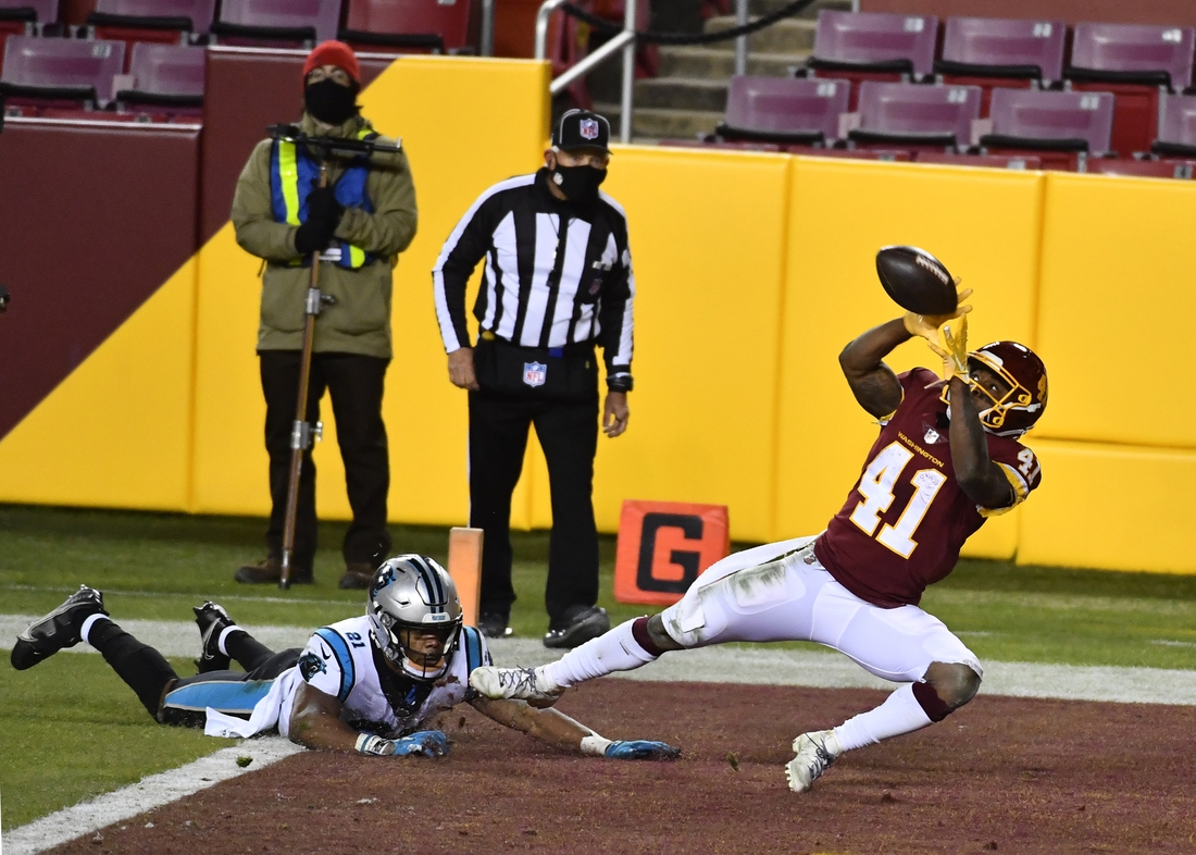 Dec 27, 2020; Landover, Maryland, USA; Washington Football Team running back J.D. McKissic (41) catches a touchdown pass as Carolina Panthers safety Jeremy Chinn (21) defends during the second half at FedExField. Mandatory Credit: Brad Mills-USA TODAY Sports