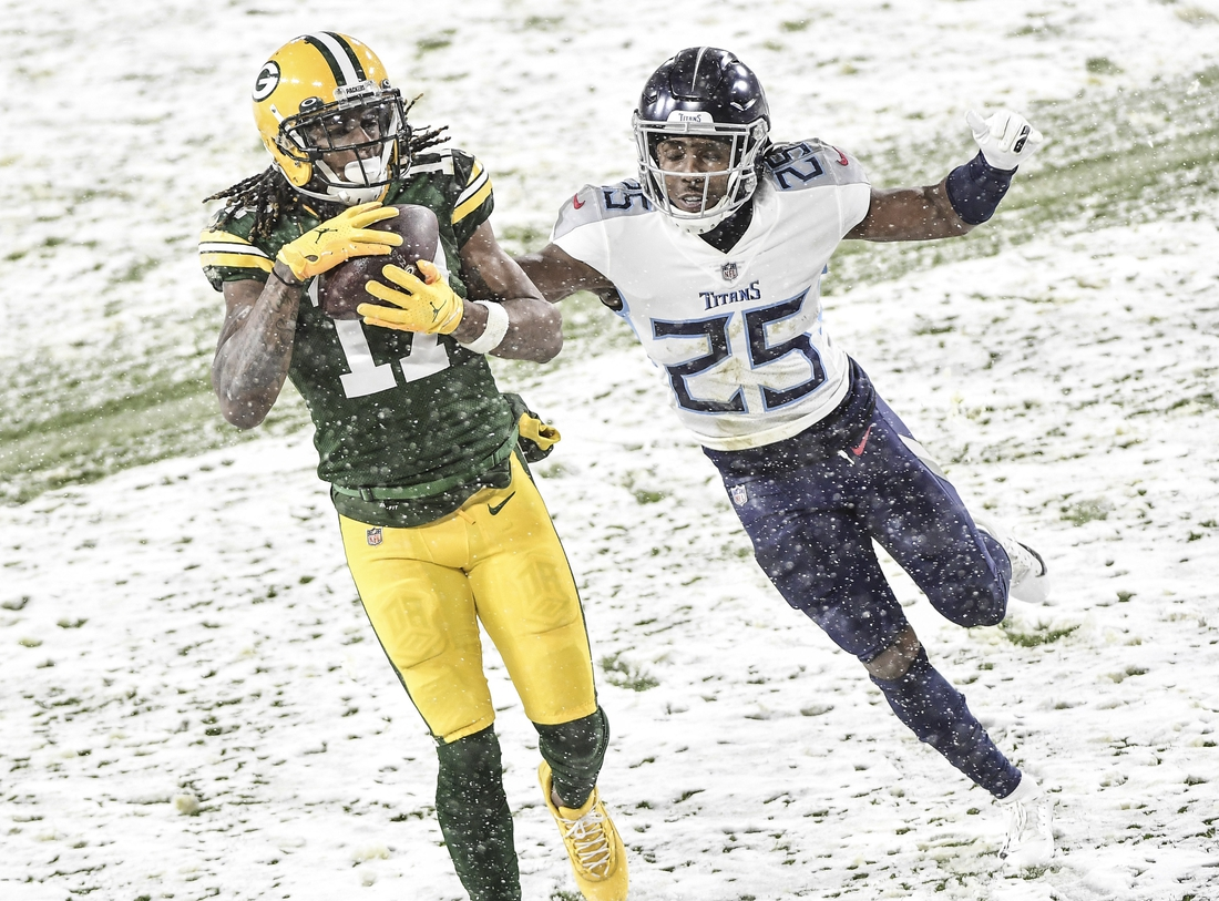 Dec 27, 2020; Green Bay, Wisconsin, USA;  Green Bay Packers wide receiver Davante Adams (17) catches a touchdown pass against Tennessee Titans cornerback Adoree' Jackson (25) in the second quarter at Lambeau Field. Mandatory Credit: Benny Sieu-USA TODAY Sports