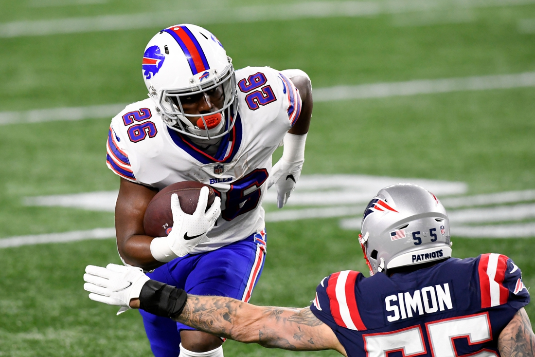 Dec 28, 2020; Foxborough, Massachusetts, USA; Buffalo Bills running back Devin Singletary (26) rushes against New England Patriots defensive end John Simon (55) during the first quarter at Gillette Stadium. Mandatory Credit: Brian Fluharty-USA TODAY Sports