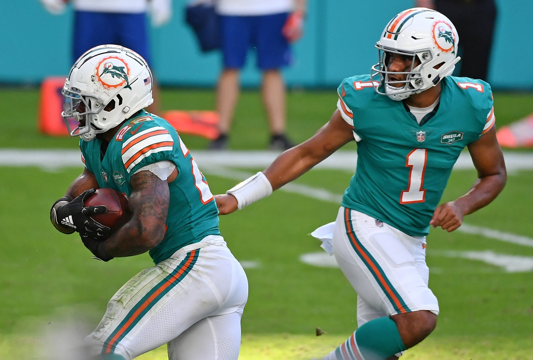 Dec 20, 2020; Miami Gardens, Florida, USA; Miami Dolphins quarterback Tua Tagovailoa (1) hands the ball to running back Salvon Ahmed (26) during the second half against the New England Patriots at Hard Rock Stadium. Mandatory Credit: Jasen Vinlove-USA TODAY Sports